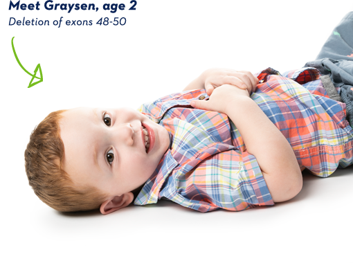 EXONDYS 51 patient Graysen, age 2, lying on floor on his back looking at camera and smiling