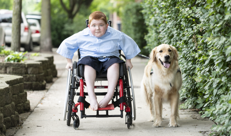 EXONDYS 51 patient Ryan, age 11, seated in wheelchair on sidewalk rolling toward camera with his Golden Retriever by his side